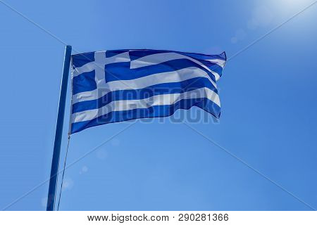 Greek Flag Waving Before Sun On Blue Sky. Diplomacy Concept, International Relations.