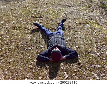Teenager Lies On The Ground In Spring In The Sun