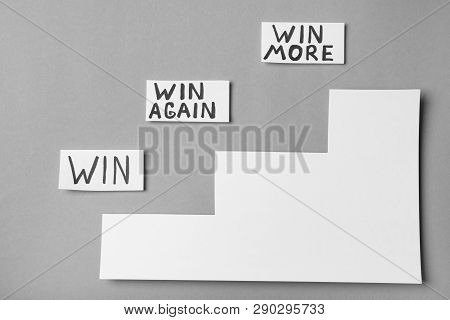 Cards With Words Win, Win Again, Win More And Paper Cutout Stairs On Grey Background, Top View. Vict