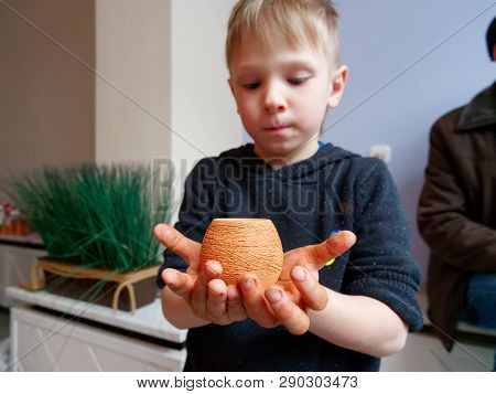 Potter Boy Proudly Holding A Clay Pot.