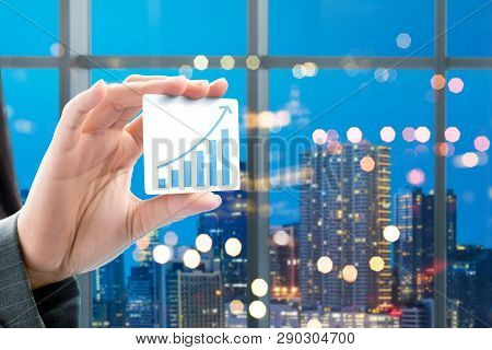 Business Woman Hand Showing White Card With Increased Graph On The Office With City At Night Backgro