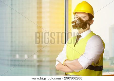 Young Asian Worker Man In Safety Vest, Gloves, Yellow Helmet And Protective Mask Standing In The Off