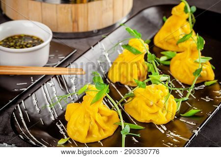 Pan-Asian cuisine concept. Wontons of yellow dough, minced meat. Japanese dumplings with minced meat. Serving dishes in the restaurant on a black plate. Background image copy space poster