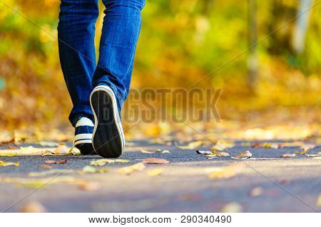 Person Wearing Casual Sneakers Shoes And Blue Jeans Trousers Walking Outdoor. Stylish Urban Fashion
