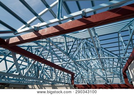 Structure Of Steel Roof Frame For Building Construction Isolated On Blue Sky Background.