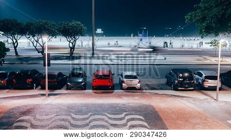 Long Exposure Of Avenida Atlantica And Busy Copacabana Beach At Night With Cariocas And Tourists Pra