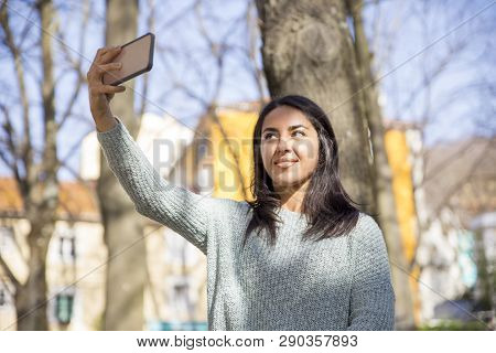 Smiling Pretty Young Woman Taking Selfie Photo Outdoors. Beautiful Lady Posing And Using Smartphone