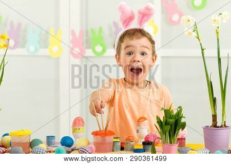 Surprised Little Child Boy With Easter Bunny Ears Painting Easter Eggs At Home. Adorable Child Prepa
