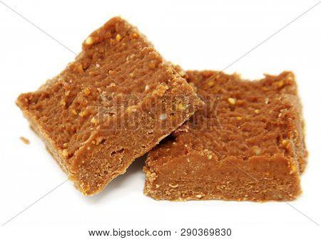 Cocoa and peanutbutter fudge keto diet fatbomb desserts over white.