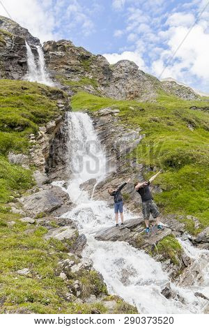A Father And Son In A Dub Dance Pose At The Alpine Waterfall In Hohe Tauern National Park In Austria