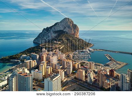 Drone Point Of View Rock Of Penon De Ifach, Harbor, Mediterranean Sea Rooftops Of Houses Calpe Citys