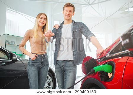 Young Smiling Family Buying First Electric Car In The Showroom. Attractive Man Holding Car Key While