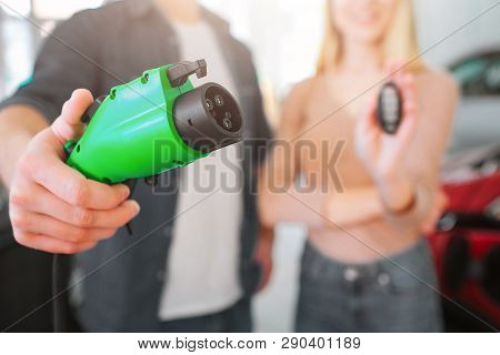 Close-up Of Green Electric Charging Plug In Hand, Electric Car Concept. Woman Holding Car Key. Young