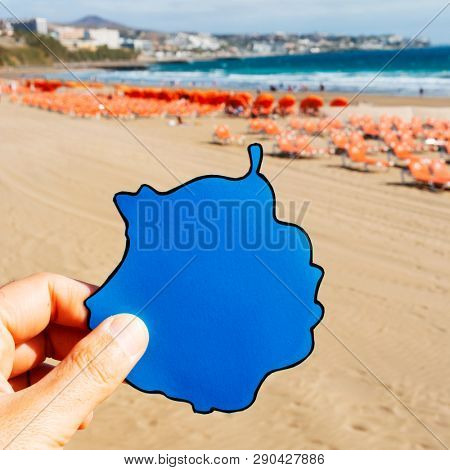 closeup of a caucasian man with the silhouette of the Gran Canaria island in his hand at the Playa del Ingles, in Maspalomas, Gran Canaria, Spain