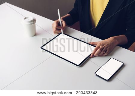 Woman Using Tablet Screen Blank And Smartphone On The Table Mock Up To Promote Your Products. Concep