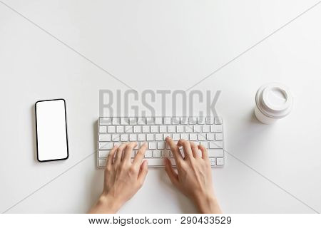 Women Hand Are Typing Keyboard And Smartphone, Coffee Cup On The Desk.
