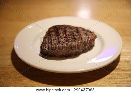 Steak dinner. Steak dinner on a white plate in a restaurant.  Dinner time