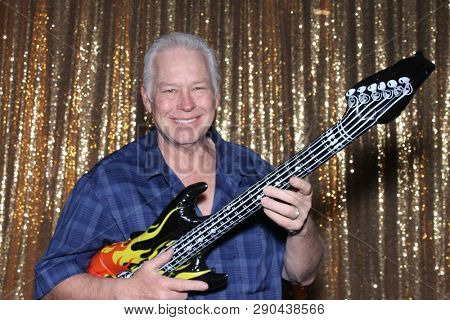 Man in a Photo Booth. A man smiles and poses with an inflatable guitar in a Photo Booth. Photo Booths are fun for all guest.
