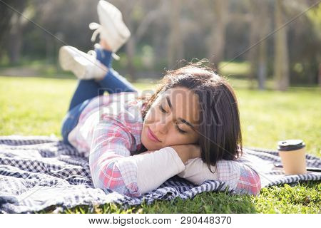 Calm Tranquil Girl Relaxing In Park. Young Woman Lying On Plaid Outdoors With Closed Eyes. Tranquili