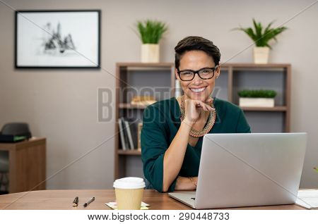 Portrait of happy casual businesswoman sitting at desk in office. Cheerful latin woman working on laptop and looking at camera. Young fashionable girl wearing eyeglasses sitting at creative agency.