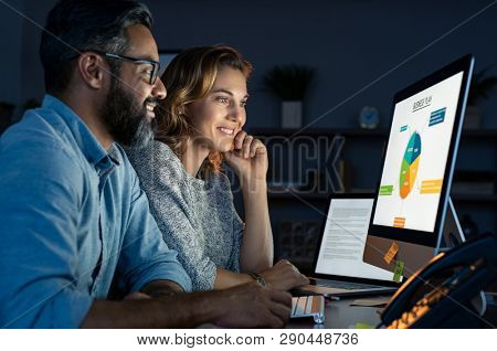 Happy business people working together in office at night. Startup business partners working late together. Mature man and casual woman working with computer late at night in their office.