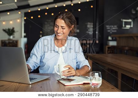 Smiling woman sitting in cafeteria holding coffee mug and working on laptop. Businesswoman checking email on laptop. Beautiful middle aged woman and using laptop at cafe while drinking a cup of tea.