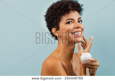 Beautiful young woman applying on skin a jar of cream. Happy brazilian woman applying hydrating moisturizer and looking at camera with copy space. Smiling african beauty isolated on blue background.