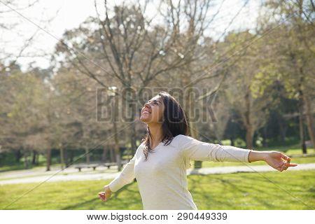 Joyful Careless Girl Enjoying Great Weather In City Park. Beautiful Young Woman In Casual Spreading