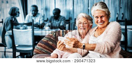 Portrait of smiling senior woman taking selfie with friend through mobile phone at nursing home