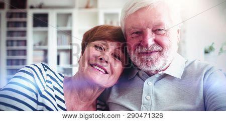 Portrait of senior couple sitting on sofa in living room