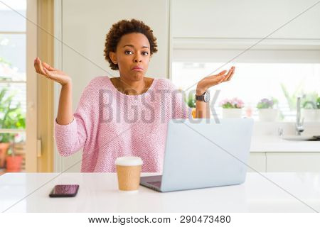 Young african american woman working using computer laptop clueless and confused expression with arms and hands raised. Doubt concept.