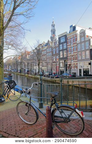 Crooked And Colorful Heritage Buildings, Located Along Bloemgracht Canal, With Westerkerk Church Clo