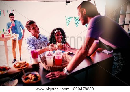 Waiter serving snacks to customers at food truck counter