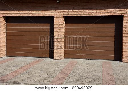 Facade Of A Brown Brick Garage With Two Gates In The Street Near The Sidewalk
