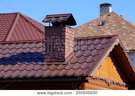 Part Of The Roof With Red Tiles And Brick Chimney