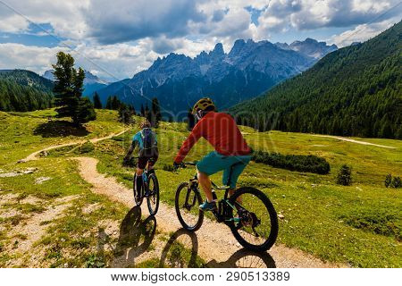 Cycling woman and man riding on bikes in Dolomites mountains landscape. Couple cycling MTB enduro trail track. Outdoor sport activity.