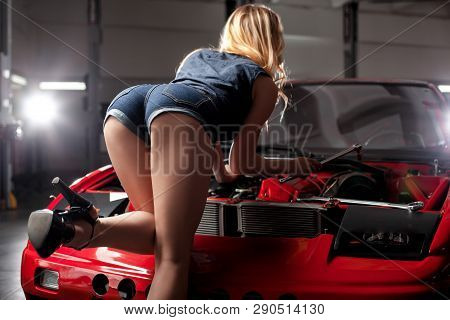 A Sensual Girl In Denim Shorts And Good Bottom, Stands In Front Of The Car Hood.