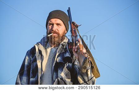 Hunter With Rifle Gun Close Up. Guy Bearded Hunter Spend Leisure Hunting And Smoking. Brutality And