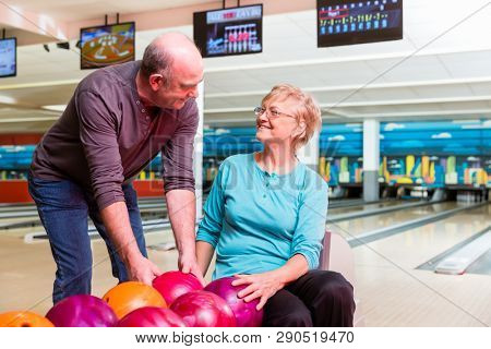 Happy mature couple looking at each other enjoying indoor games