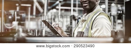 Portrait of smiling factory worker writing on clipboard in factory