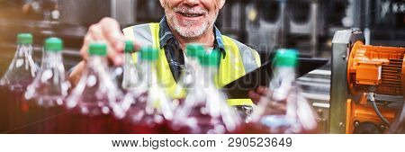 Portrait of male factory worker monitoring cold drink bottles at drinks production factory