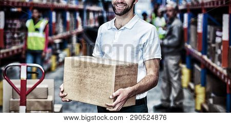 Portrait of worker is holding cardboard boxes and smiling to the camera in a warehouse