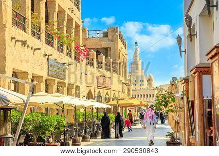 Doha, Qatar - February 20, 2019: Women And Men In Traditional Arab Clothing Walk Along Main Street I