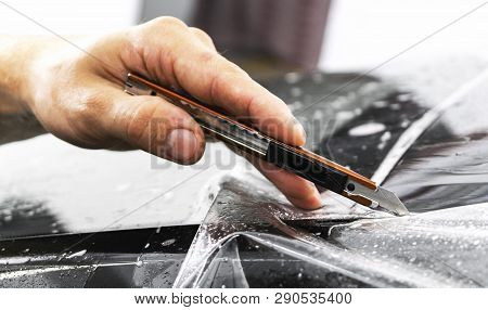 Car Wrapping Specialist Cutting Vinyl Foil Or Film On Car. Protective Film. Applying A Protective Fi