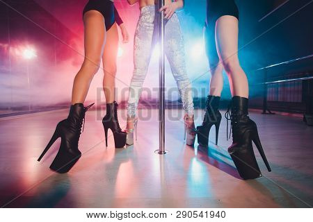 Young Striptease Dancers Moving In High Heels Shoes On Stage In Strip Night Club, Pole Dancing.