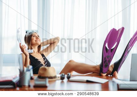 Woman in flippers at table in office, daydreaming