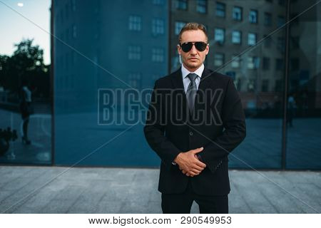 Male bodyguard in suit, earpiece and sunglasses