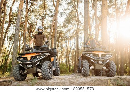 Two atv riders in helmets raise their hands up