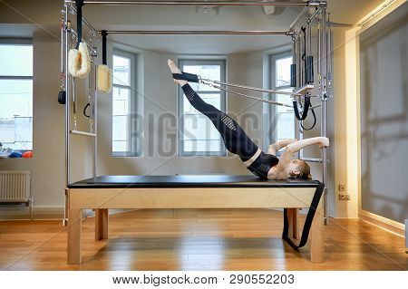 Gym Woman Pilates Stretching Sport In Reformer Bed Instructor Girl. Healthy Smiling Woman Wearing Le