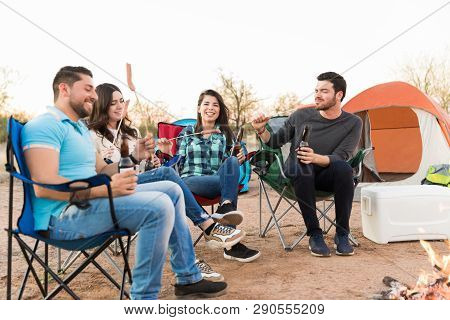 Smiling Beautiful Woman With Young Pals Having Food And Drink At Campsite